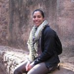 Alissa King sitting near a stone wall in India